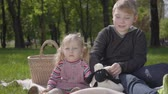 čtenář : Teenage blond boy sitting on the blanket in the park reading the book to her little sister in pink dress who sitting near. The girl is not interested in the story, she wants to play. Children on the picnic