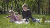 piccolo : Teenage blond boy sitting on the blanket in the park reading the book to her little sister in pink dress who sitting near. The girl is not interested in the story, she wants to play. Children on the picnic