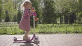 всадник : Little funny girl in a pink dress riding a scooter in the park. Camera following the child. Active lifestyle, leisure outdoors, carefree childhood