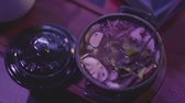 udon : Tasty soup with mushrooms and noodles in a metal bowl with a lid on the table in the night club in blue light close-up. Party lifestyle. Healthy food concept Stock Footage
