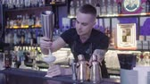 nata : Young barman grating small kiwi on a grater over a glass of creamy cocktail standing on the bar counter. Long shelf with elite alcohol in the background. Night lifestyle