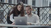 venkovní : Bearded young man sitting at the table on the terrace in front of the laptop, working. Pretty girl bent near looking on the screen, smiling. Concept of freelance, distant work. The guy doing business