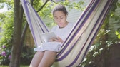 függőágy : Young African American woman sitting in the hammock, relaxing in the garden, texting on her new tablet. Leisure outdoors. Addiction to gadgets