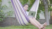 chatten : Young African American woman sitting in the hammock, relaxing in the garden, texting on cell phone. Leisure outdoors. Addiction to gadgets