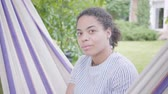chatten : Close up portrait of young smiling African American woman sitting in the hammock, relaxing in the garden, texting on notebook. Leisure outdoors.