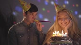 background color : Portrait of a handsome guy and a girl celebrating his birthday sitting at a table with a cake. Burning candles on background of multi-colored blinks on the wall.