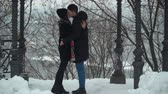 cappotto : Beautiful young woman and man kissing passionately in winter park covered with snow Happy couple in love enjoy time together. Winter leisure. Camera moves closer, zooming