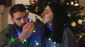 pohlazení : Man and woman sitting near new year tree with a garland around the neck. Girl caress hair of her boyfriend, beardie kiss her cheek. Happy adult couple have christmas fun. Concept of leisure at home