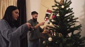 семья : Young positive couple decorating the Christmas tree in the room before the holiday. New Year and Christmas time concept. Happy family preparing for holidays