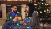 kamin : Man and woman sitting near new year tree with a garland around the neck close up. Man gives present to woman, she surprised and happy, lovers kissing. Happy couple have christmas fun. Concept of leisure at home Stock Footage