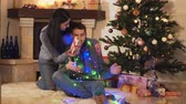 husband : Young positive couple sitting at the Christmas tree on the floor in the room. The woman giving the gift box to the man. New Year and Christmas time concept. Happy family celebrating holidays Stock Footage