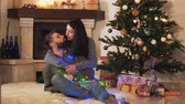 husband : Young positive couple sitting at the Christmas tree on the floor in the room. New Year and Christmas time concept. Happy family celebrating holidays