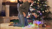 kamin : Man and woman in home clothes decorating christmas tree at home. Happy couple preparing for Christmas party. Concept of leisure at home before holidays Stock Footage