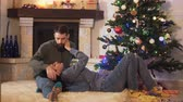 семья : Young pretty couple lying at the Christmas tree together. New Year and Christmas concept Стоковые видеозаписи
