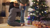 anno : Young positive couple decorating the Christmas tree together in the room before holiday. New Year and Christmas time concept Filmati Stock