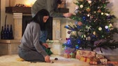 семья : Man and woman in home clothes decorating new year tree in modern room. Girl gives toys, man hanging them on branches. Happy couple prepare for Christmas party. Concept of leisure at home before holidays