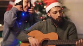 сочельник : Man playing guitar and singing sitting on the floor near christmas tree in modern room. Happy couple prepare for Christmas Стоковые видеозаписи