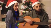 сочельник : Portrait of happy couple in Santas hats singing songs at home. Man playing guitar. Woman with garland on her neck sitting near husband. Christmas tree in the background. Family celebrating Christmas Стоковые видеозаписи