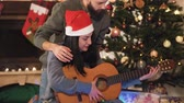 сочельник : Portrait of happy couple in Santas hats on Christmas eve. Man teaching woman to play guitar. Christmas tree in the background. Family celebrating New Year together Стоковые видеозаписи