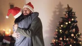 husband : Young positive couple in Santa hats dancing and hugging in the room in front of the Christmas tree. New Year and Christmas time concept. Happy friendly family celebrating winter holidays Stock Footage