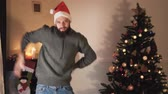 mudanza : Funny bearded man dancing near the christmas tree. Happy handsome man in Santas hat moves his body in funny way. Pretty brunette woman joins him, making joking moves. Couple has christmas fun