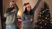 husband : Young positive couple in Santa hats dancing and jumping in the room in front of the Christmas tree. The man and the girl taking off their hats and throwing up. New Year and Christmas time concept. Happy family celebrating winter holidays Stock Footage