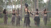 ninfa : Group of women dancers with make-up and in mystical fabulous costumes dancing groovy dance in the forest. Forest fairies, dryads have fun among the trees. Performance of dancers outdoor.