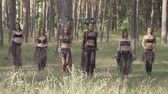 dansçı : Beautiful young women in theatrical costumes of devil or maleficent dancing belly dance in forest showing perfomance or making ritual Stok Video