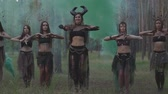 executante : Beautiful young women in theatrical costumes of devil or maleficent dancing in forest showing perfomance or making ritual on the background of holi paints Stock Footage