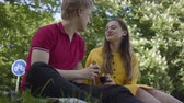 amante : Happy young couple in love making picnic with wine in beautiful blooming garden or park cheerfully chatting and smiling Stock Footage