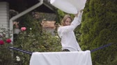 keten : Funny cute young woman have fun dancing at the backyard while doing house work with the linen. Washday, washing day Stok Video