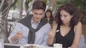 biscoitos : Portrait of the happy couple eating desert sitting in cafe outdoors. Young man and woman sitting together enjoying their meal. Date concept Stock Footage