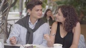 nata : Portrait of happy couple eating dessert sitting in cafe outdoors. Young man and woman together enjoying their meal. The woman feeding her boyfriend. Date concept