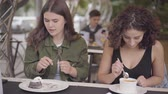 nata : Portrait of two girlfriends trying cakes sitting in the cafe outdoors. Young girls together enjoying their meals talking and laughing. Leisure outdoors, friendly relationship