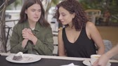 nata : Two girlfriends trying cakes sitting in cafe outdoors. Waitress bringing a plate with dessert and putting on the table. Young girls together enjoying their meals. Leisure outdoors, friendly relationship Vídeos
