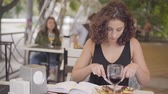 роскошный : Young beautiful curly woman eating tasty meat food at the street cafe. The girl enjoying her meal relaxing outdoors. The lady cutting cutlet with fork and knife. Leisure outdoors Стоковые видеозаписи