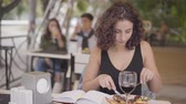 роскошный : Young beautiful curly woman eating tasty meat dish at street cafe. The girl enjoying dessert relaxing outdoors. Girl enjoys a meal. Leisure outdoor.