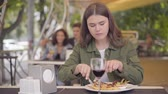 роскошный : Young beautiful woman in casual clothes eating meat and drinking red wine at the street cafe. The girl enjoying food relaxing outdoors. The lady sitting at the table cutting cutlet with fork and knife