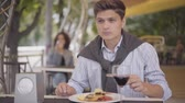 роскошный : Young man eating tasty meat food at a street cafe and drinking red wine. The girl enjoying his meal relaxing outdoors. The guy cutting cutlet with fork and knife. Leisure outdoors