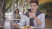 роскошный : Young man eating tasty meat food at a street cafe and enjoying elite red wine. The man enjoying his meal relaxing outdoors. The guy cutting cutlet with fork and knife. Leisure outdoors Стоковые видеозаписи