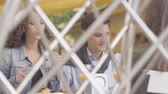 даты : The happy couple enjoying their dinner relaxing in cafe. The curly woman sharing her food with boyfriend. Shooting from behind the fence. Leisure together, date concept
