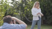oturum : Backstage of the photo shoot. Professional photographer taking photos of elegant woman in white shirt and jeans posing outdoors. Male photographer taking photos of attractive woman n the backyard
