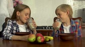 cruche : The boy and girl drinking milk from transparent glasses. Siblings enjoy their healthy beverage sitting in the modern kitchen at the table. Healthy lifestyle, happy family Vidéos Libres De Droits