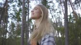 спин : Portrait of cheerful beautiful girl in plaid shirt and hipster outfit smiling and spinning around herself on the background of beautiful forest. Slow motion