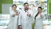 köntös : Three young caucasian pharmacists showing thumbs up to the camera and smiling. Highly professional employees staying at their workplace. People in white robes aimed at rescuing lives