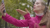 запустить : Portrait of smiling Caucasian woman in pink sportswear sending air kisses via smart phone and starting running. Female runner training in the morning outdoors. Sports concept