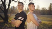 konkurenční : Two young Caucasian bodybuilders standing in sunlight and looking at camera. Handsome strong sportsmen spending time in the autumn park. Healthy lifestyle, sport concept