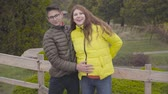 Teenage Caucasian boy in eyeglasses caressing belly of his smiling pregnant mother in yellow coat. Happy mother spending autumn day with her adult son outdoors. Good relationship, leisure