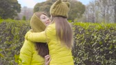 Close-up of young Caucasian woman talking to her daughter dressed in similar yelllow coat and mustard hat. Mother and daughter rubbing noses and smiling. Happy family spending autumn day outdoors