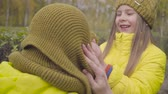 Smiling Caucasian girl fixing mustard scarf on mothers head. Woman with daughter dressed in similar yellow coats having fun outdoors. Family spending autumn day together